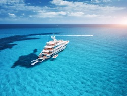 Yacht on the azure seashore in balearic islands. Aerial view of floating boat with people in transparent sea at sunset in summer. Top view from drone. Seascape with luxury yachts in bay. Travel