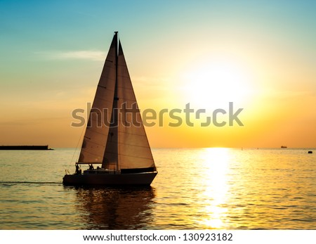 Yacht sailing against sunset. Holiday lifestyle landscape with skyline sailboat and sunset silhouette. Yachting tourism - maritime evening walk. Romantic trip on luxury yacht during the sea sunset.