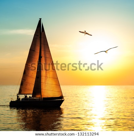 Yacht sailing against sunset. Holiday lifestyle landscape with skyline sailboat and two seagull. Yachting tourism - maritime evening walk. Romantic trip on luxury yacht during the sea sunset. Сток-фото ©