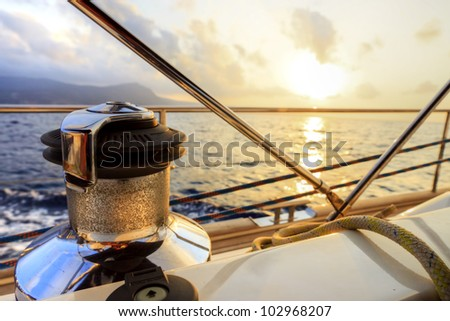 Yacht sailing along the coast at sunset