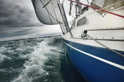 Yacht sailing in a thunderstorm on a rainy day. Close-up view from the deck to the bow, mast and sails. Dramatic stormy sky, dark clouds. Waves and water splashes. Rough weather. Baltic sea, Sweden