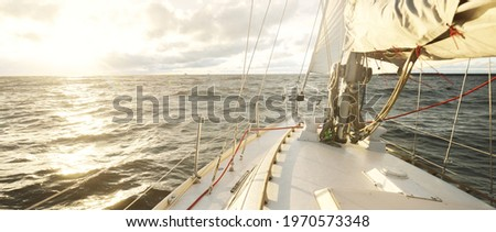 Yacht sailing in an open sea at sunset. Close-up view from the deck to the bow, mast and sails. Dramatic stormy sky, golden clouds, winter cyclone, rough weather. Epic seascape. North sea, Norway Stock photo ©