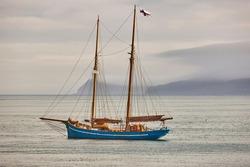 Yacht sailing on Faroe island fjords. Atlantic ocean coastline. Travelling