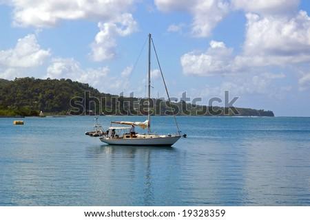 yacht sailing onto tropical harbor