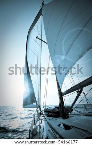 yacht sailing towards sunset - picture in blue tone
