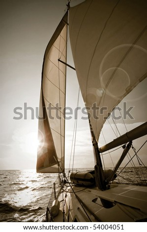 yacht sailing towards sunset - picture in sepia tone