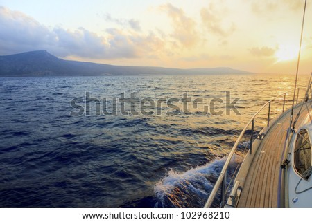 Yacht sailing towards the sunset