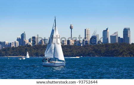 yacht sails sydney harbour blue water and sky with cityscape background and green part trees