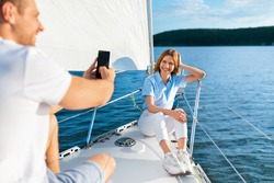 Yacht Tour. Husband Taking Picture Of Wife Relaxing On Sailboat Sailing In Sea. Summer Adventure. Selective Focus