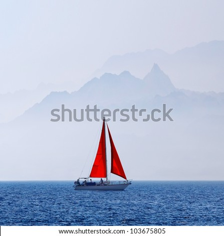 Yacht with a red sail on a mountain background in the sea