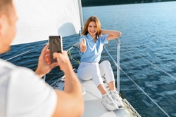 Yachting. Wife Gesturing Thumbs Up While Husband Taking Photo On Smartphone Outdoor. Couple Having Fun Relaxing On Sailboat In Sea. Romantic Summer Adventure, Dream Vacation. Selective Focus