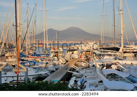 Yachts anchored in the marina of Naples at sunset with Mt.Vesuvius in the background