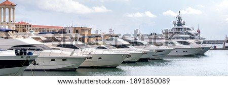Yachts and speed boats at harbor. Power boats moored in marina. Sea coast pier. High class lifestyle. Yachting. Expensive toys. Sea transport. Journey. Expensive boats at the pier. Stock fotó ©
