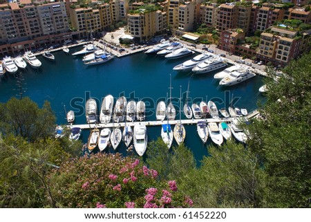 Yachts moored in a sunny marina in Monaco with surrounded by buildings.