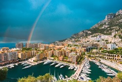 Yachts moored near city Pier, Jetty In Sunny Summer Day. Monaco, Monte Carlo architecture. Altered Sky With rainbow.