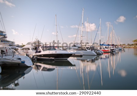 Yachts mooring at a wharf. Sky is blue with some clouds and smooth water surface reflects mirror image of yachts and sky.
