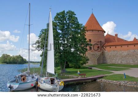 yachts parked near Mediterranean castle of red brick on lake famous tourist place lietuva trakai