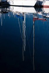 Yachts with reflections at the pier. Smooth wavy water with reflection. Sky and yacht masts reflected on the water surface.