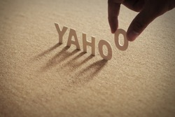 YAHOO wood word on compressed or corkboard with human's finger at O letter.
