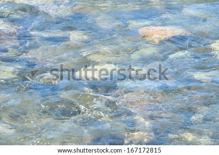 Yakutsk river in the mountains. Photo texture the surface of the transparent water flowing against the background of multicolored pebbles on the bottom.