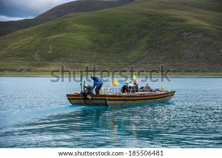 Yamdrok Lake in Tibet, China./Man on a boat in Yamdrok lake/Tibet, China -September 3, 2013: Transportation people and goods by small wooden boat at September 3, 2013 in  Yamdrok Lake in Tibet, China.