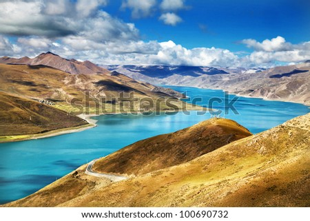 Yamdrok-tso lake shines on sunny blue sky day in Tibet