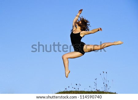 Yang ballet woman in training suit performs outdoor in sunset time.