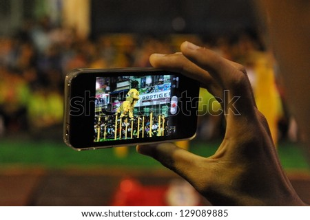 YANGON - FEB 11: A spectator uses a smartphone to video a lion dance on a downtown street during celebrations ushering in the Chinese new year of the snake on Feb 11, 2013 in Yangon, Burma.