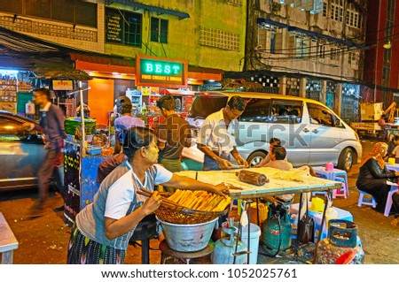 YANGON, MYANMAR - FEBRUARY 14, 2018: The cooks in street kitchen of Chinatown outdoor cafe prepare deep fried pies, on February 14 in Yangon. #1052025761