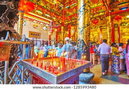 YANGON, MYANMAR - FEBRUARY 17, 2018: The view on crowded prayer hall of Kheng Hock Keong Temple of Sea Goddess Mazu behind the burning candles, on February 17 in Yangon. #1285993480