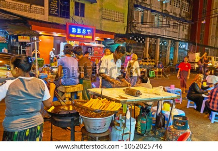YANGON, MYANMAR - FEBRUARY 14, 2018: Traditional street food in Maha Bandula road cafe of Chinatown - cooks knead and mold the dough, then prepare crispy pies in deep fryer, on February 14 in Yangon. #1052025746