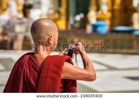 YANGON, MYANMAR - JANUARY 3, 2014: Buddhist monk taking photos with digital point-and-shoot camera in Shwedagon Paya pagoda
