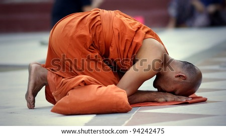 YANGON, MYANMAR - NOV 15: An unidentified buddhist monk kneels down in prayer on Nov 15, 2011 in Yangon, Myanmar.