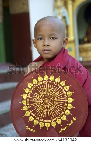 YANGON, MYANMAR - OCT 14 : Thin, 5, from Yangon waits with a fan until the end of his Buddhist naming ceremony at Shwedagon Pagoda, Yangon, Myanmar at Oct 14, 2010.