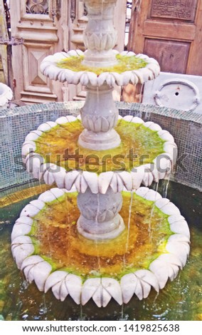 Yard antique shop. Ancient oriental fountain of white marble. Dirty green water at the source. Old stone cascade fountain. Historical background, selective focus image.  #1419825638