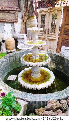 Yard antique shop. Ancient oriental fountain of white marble. Dirty green water at the source. Old stone cascade fountain. Historical background, selective focus image.  #1419825641