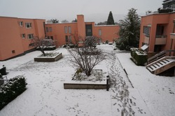 Yard in winter under snow. The snow has not been cleared away, there are shoe imprints. They imply danger of accident on the slippery ground, due to lack of maintenance.
