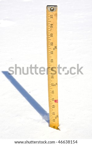 Yardstick measuring the depth of snow and shadow behind it  showing the strong sun's warm rays after the storm.