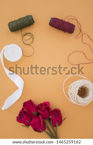 Yarn spools; white ribbon; string spool and red roses on an orange backdrop #1465259162