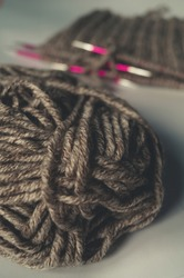 Yarn thread hairs close up on a blurry background of knitting needles