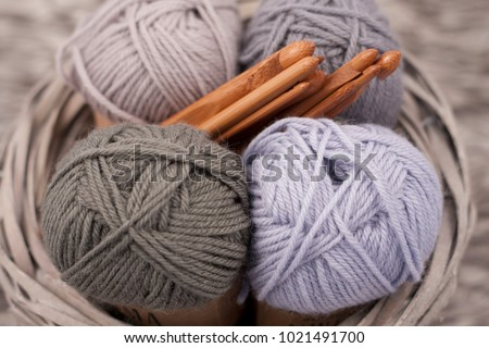 Yarns in basket with crochet hooks in harmonious colors.\nknitting, crocheting supplies.