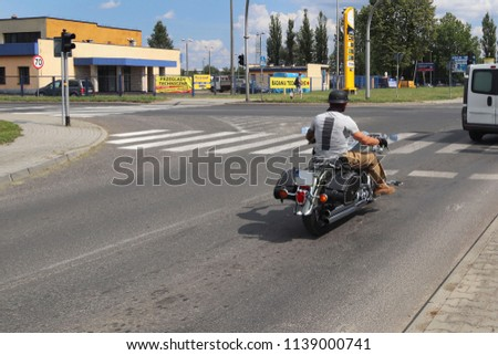 Yaslo, Poland - july 12 2018:The biker rides a stylish chopper on an asphalt road. Cruise on an iron horse. The life style of the pilgrim. A romantic soul with a strong male body. Adrenaline speed.