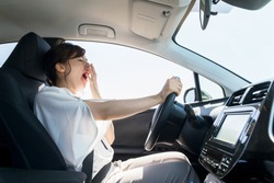 yawning female driver. falling asleep at the wheel concept.