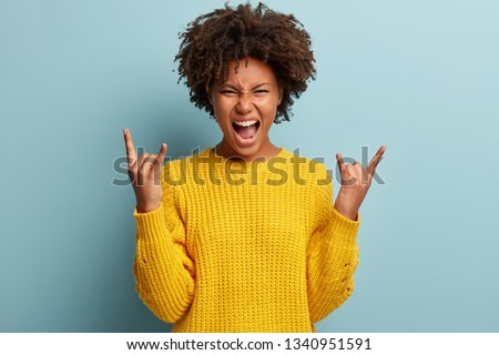 Yeah, feeling cool and awesome. Excited happy young African American woman lifts mood from loud music, shows rock n roll gesture, glad to visit concert of favourite band, exclaims loudly with joy.