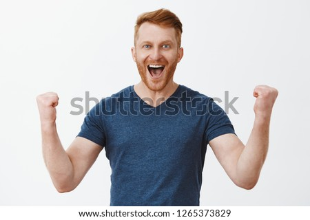 Yeah, good work man. Happy cheerful good-looking redhead strong man, raising clenched fists in hooray gesture, smiling broadly, triumphing from successful deal or great news, being joyful and thrilled