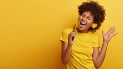 Yeah, I am pleased. Joyful lovely dark skinned woman raises hand in dance move, likes great sound in new headphones, sings loudly, carries cellular, smiles broadly, wears yellow casual clothes
