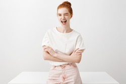 Yeah live on bright side. Portrait of charming carefree redhead female student in pink jeans and trendy t-shirt, winking flirty at camera and smiling joyfully, leaning on table, relaxing and chilling