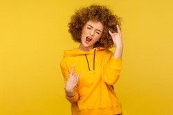 Yeah, that`s wonderful! Portrait of overjoyed curly-haired woman in urban style hoodie showing rock and roll hand sign, screaming and gesturing to heavy metal, rock music. indoor studio shot isolated