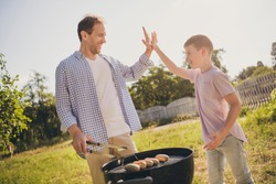 Yeah we did it. Father son relationship concept dad daddy cook grill meat sausages prepare lunch preteen boy kid give high-five enjoy victory outside city in summer park garden