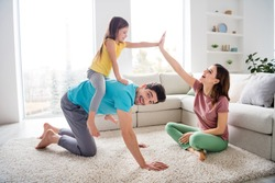 Yeah you ride horse. Fun three people play game little kid girl sit piggyback dad clap hand high five mom on floor carpet in house indoors